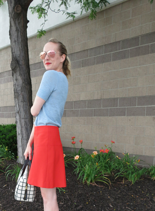 pale blue sweater, red flared skirt, windowpane bag, pink Ray Ban aviators, nude sandals