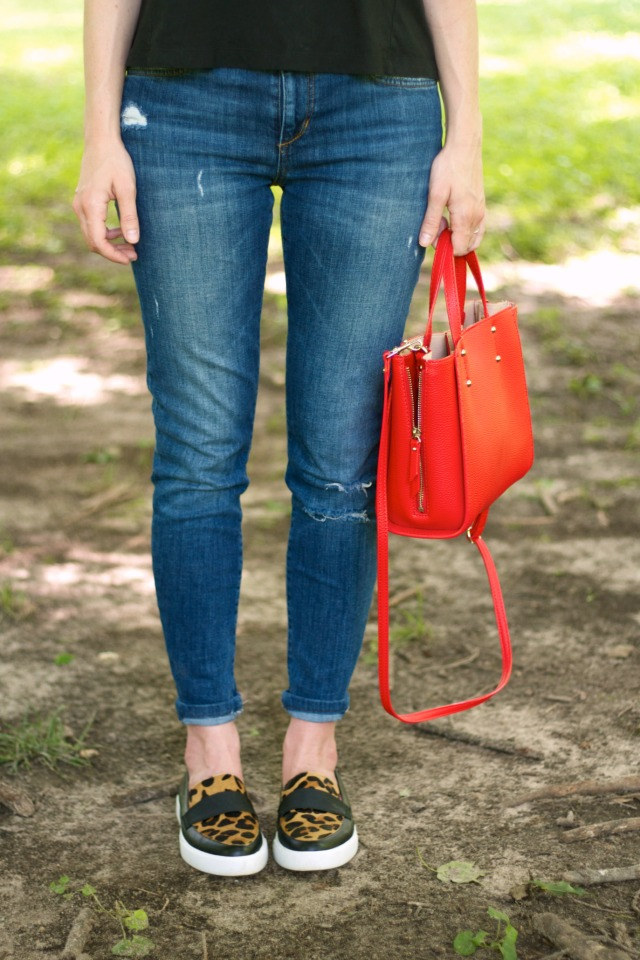 distressed jeans, graphic tee, red satchel, leopard sneakers
