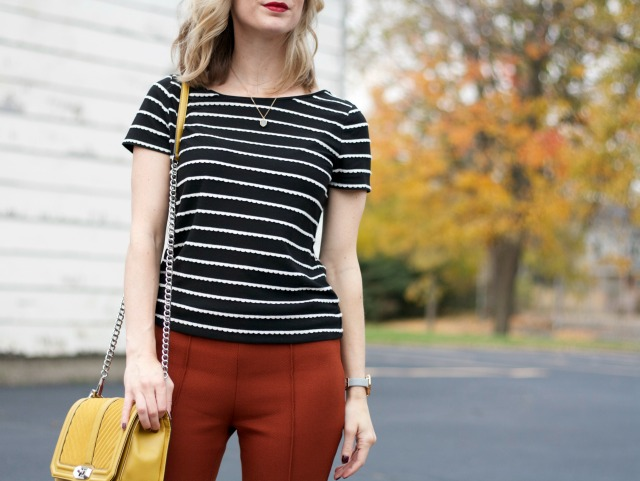 rust colored ankle pants, black and white stripe tee, yellow Rebecca Minkoff bag, Skagen watch, cap toe flats