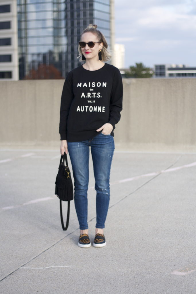 graphic sweatshirt, distressed jeans, leopard sneakers, tassel earrings