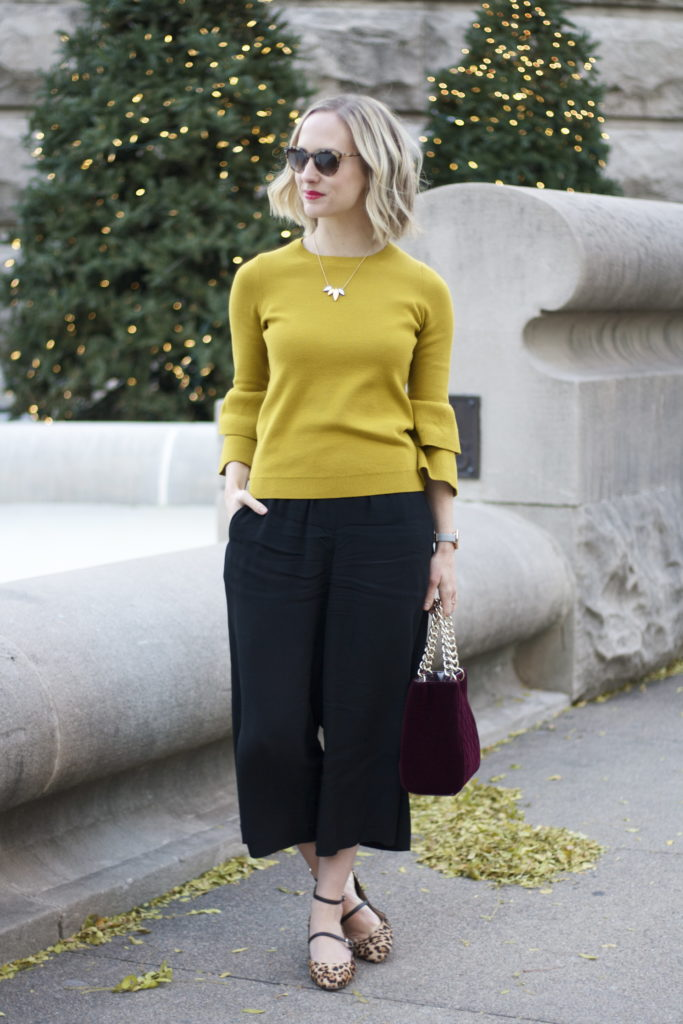 chartreuse bell sleeve sweater, culottes, strappy leopard pumps, velvet bag